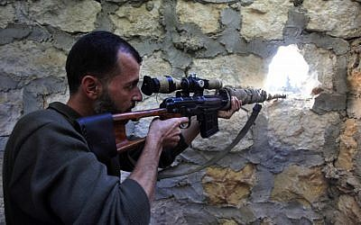 A rebel sniper aims at a Syrian army position on the outskirts of Aleppo, Syria, Wednesday, Nov. 14, 2012. (photo credit:AP Photo/Khalil Hamra)