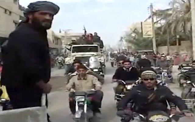 Syrian rebels celebrating the takeover of Mayadeen military base near Deir el-Zour, Thursday, Nov. 22 (photo credit: AP/Shaam News Network)