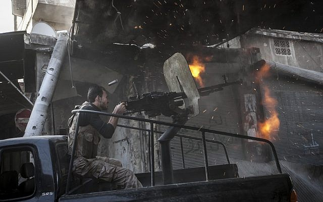 A member of the Syrian opposition fires at regime forces in Aleppo, Sunday (photo credit: Narciso Contreras/AP)