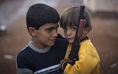 Two Syrian boys who fled with their families from the violence in their village, look on as one holds a toy gun at a displaced persons camp in Atmeh, near the Turkish border with Syria, on Thursday (AP/Khalil Hamra)