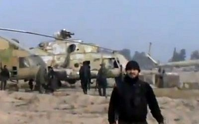 In this image taken from a video, Syrian rebels are shown capturing a helicopter air base near Damascus on Sunday (photo credit: AP/Ugarit News via AP video)