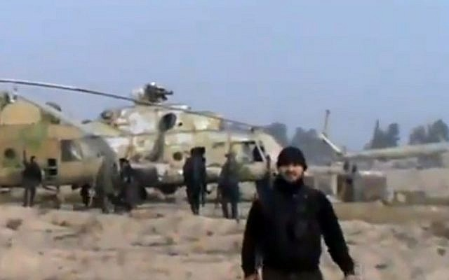 This video image shows Syrian rebels with a captured helicopter at an air base near the capital Damascus in November, 2012 (photo credit: AP Photo/Ugarit News via AP video)