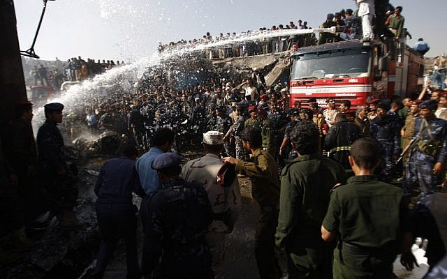 Firefighters work to extinguish a fire at the wreckage of a plane after it crashed in Sanaa, Yemen, on Wednesday, November 21, 2012 (photo credit: AP Photo/Hani Mohammed)