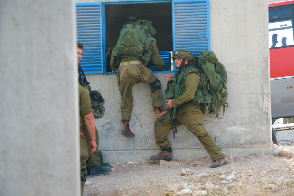 A soldier training for the Gaza Strip, helping a buddy through the window of home (Photo credit: Alon)