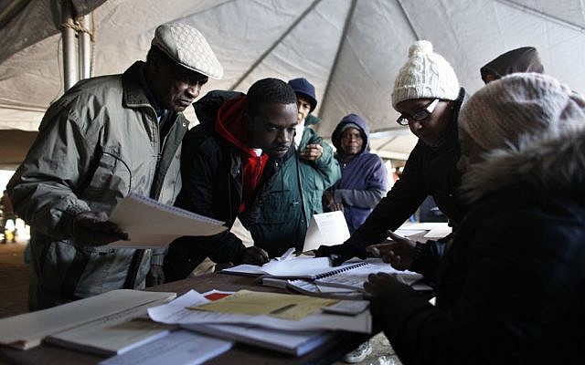 Voters check in before casting their ballots under a tent at a consolidated polling station for residents of the Rockaways on Election Day, Tuesday, Nov. 6, 2012, in the Queens borough of New York. (Photo credit: Jason DeCrow/AP)