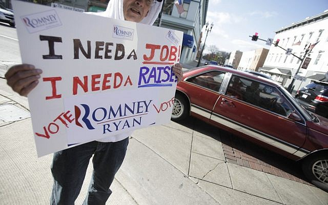 John DeNoyelles, from Flint, Texas, who said he is in Ohio trying to network to find a job, holds a sign in support of Mitt Romney along Main Street in Bowling Green, Ohio Monday Nov. 5, 2012. (photo credit: J.D. Pooley/AP)