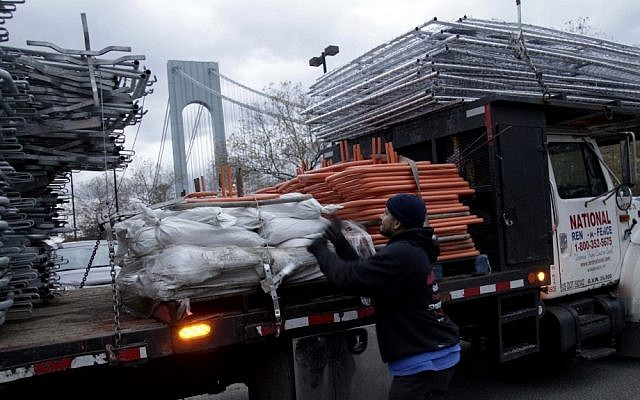 Pedro Cabrera stops setting up a barrier near the starting line of the NYC Marathon in Staten Island and secures his company's gear after the cancellation of the race on Friday (photo credit: AP/Seth Wenig)