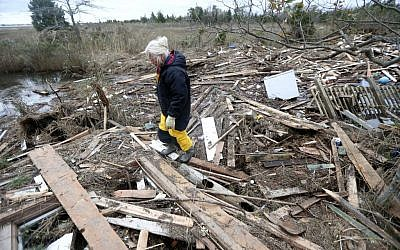 Tricia Burke walks over debris which washed up onto her property in the wake of superstorm Sandy, Thursday, Nov. 1, 2012, in Brick, N.J. (photo credit: Julio Cortez/AP)