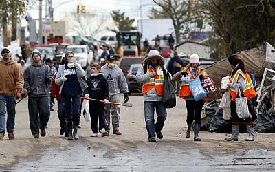 Volunteers walk toward homes to help residents clean up, Saturday, Nov. 3, 2012, in Staten Island, N.Y. (photo credit: AP/Julio Cortez)