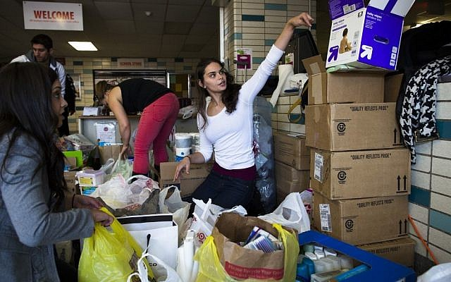 A volunteer helps sort through donations at Hoboken High School in Hoboken, New Jersey, on Sunday as surrounding neighborhoods remain without power due to damage caused by superstorm Sandy (photo credit: AP/John Minchillo)