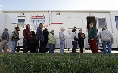 People, many displaced by superstorm Sandy, line up to vote Monday, Nov. 5, 2012, in Burlington, N.J., at a Mobile Voting Precinct. Many victims displaced by the storm are taking advantage of offers to vote early (photo credit: AP Photo/Mel Evans)