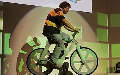 Izhar Gafni rides the cardboard bicycle he developed for the first time in public on stage at Microsoft's ThinkNext event. (Photo credit: Dror Garti/Flash90)