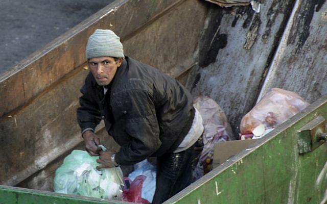 A man searching through garbage in Jerusalem (photo credit: Nati Shohat/Flash90)