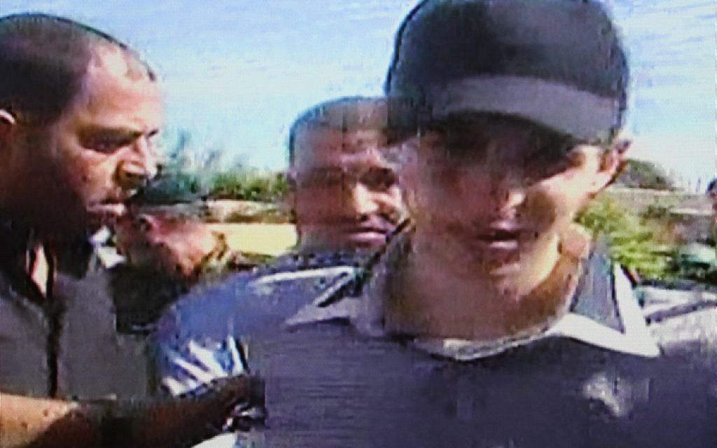 Israeli soldier Gilad Shalit (center) on the day he was released in a prisoner exchange, October 18, 2011. Hamas military leader Ahmed Jabari can be seen directly behind his right shoulder. (photo credit: Flash90)