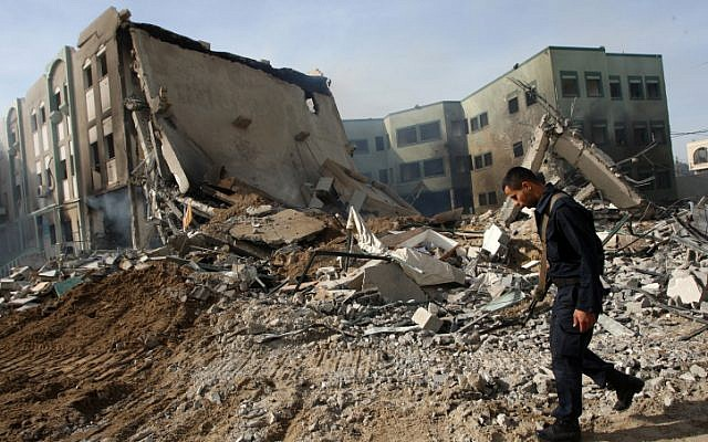 Hamas security members inspect a destroyed government building after an Israeli airstrike in Gaza City on November 16 (photo credit: Abed Rahim Khatib/Flash90)