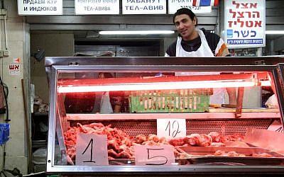 Illustrative: A butcher at the Carmel Market in Tel Aviv (Photo credit Nicky Kelvin/Flash90)