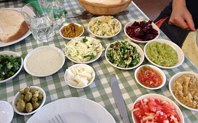A dazzling array of salads served with a hunk of old-fashioned 'black bread' at Adon Cohen (photo credit: Jessica Steinberg/Times of Israel)