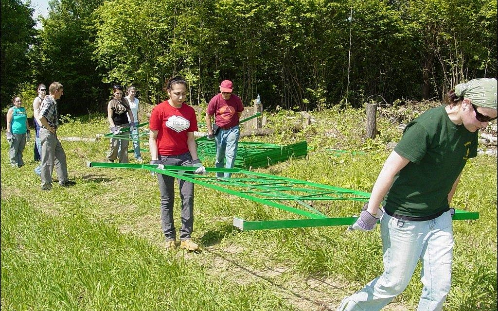 College students, roughly a third of them Jewish, help Lozman place fences around abandoned Jewish graveyards. Many receive course credit for academic work they do to prepare. (Courtesy of Michael Lozman)