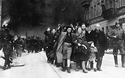Jews in the Warsaw Ghetto are led by German soldiers to an assembly point for deportation to death camps, 1943. (Public domain)
