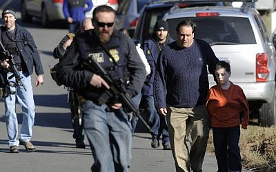 Parents leave a staging area after being reunited with their children following a shooting at the Sandy Hook Elementary School in Newtown, Conn., about 60 miles (96 kilometers) northeast of New York City, Friday, Dec. 14 (photo credit: AP/Jessica Hill)