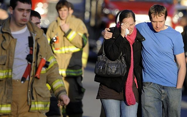 A victim's family leaves a firehouse staging area following a shooting at the Sandy Hook School in Newtown, Connecticut, where authorities say a gunman opened fire, leaving 27 people dead, including 20 children in 2012. (photo credit: AP/Jessica Hill)