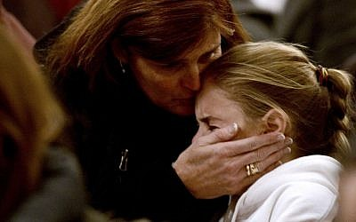 A woman comforts a young girl during a vigil service for victims of the Sandy Hook Elementary shooting, Friday, Dec. 14, 2012, at St. Rose of Lima Roman Catholic Church in Newtown, Conn. (AP Photo/Andrew Gombert)