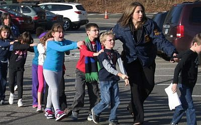 In this photo provided by the Newtown Bee, Connecticut State Police lead a line of children from the Sandy Hook Elementary School in Newtown, Connecticut on December 14, 2012 after a shooting at the school. (AP Photo/Newtown Bee, Shannon Hicks)