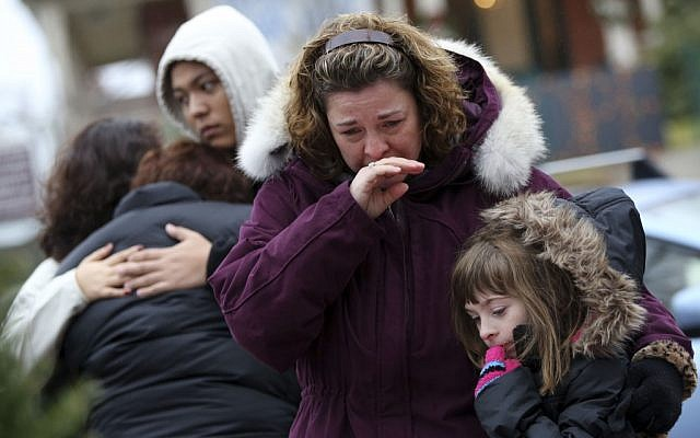Mourners grieve at one of the makeshift memorials for victims of the Sandy Hook Elementary School shooting on Sunday. (photo credit: AP/Mary Altaffer)