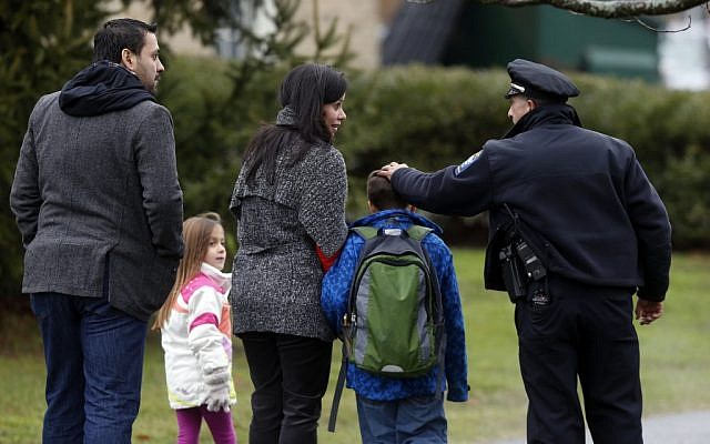 A police officer greets a returning student as he is walked into Hawley School in Newtown, Conn., Tuesday, Dec. 18, 2012. (photo credit: Jason DeCrow/AP)