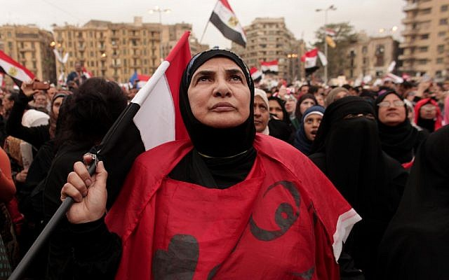 An Egyptian woman holds a national flag as she listens to speakers, not pictured, in Tahrir Square in Cairo, Egypt, Tuesday, Dec. 4, 2012 (photo credit: AP/Maya Alleruzzo)