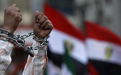 A protester shows his chained hands during a demonstration in Tahrir Square in Cairo, Egypt, on Friday against a constitution drafted by Islamist supporters of President Mohammed Morsi (photo credit: AP/Petr David Josek)