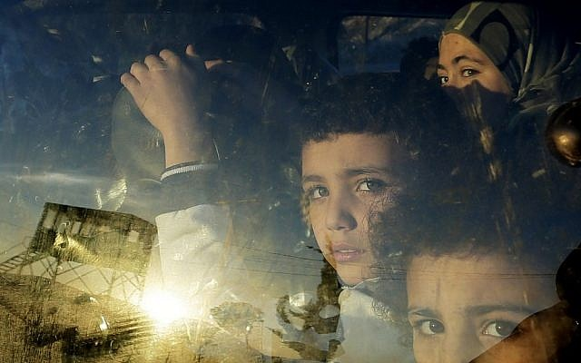 Syrian children look through their car window as they cross into Lebanon with their families at the border crossing, in Masnaa, eastern Lebanon, on Friday. (photo credit: AP Photo/Hassan Ammar)