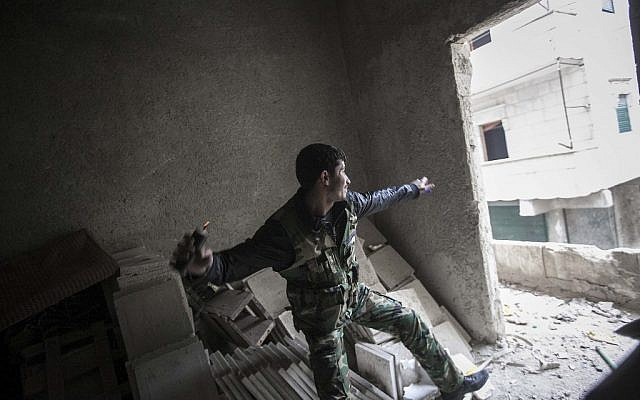 A rebel fighter throws a grenade toward Syrian troops loyal to President Bashar Assad during clashes in Aleppo, Syria, on Friday, Dec. 7 (photo credit: AP/Narciso Contreras)