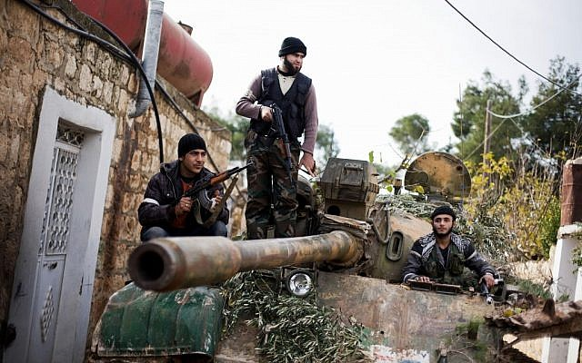 Kurdish members of the FSA are seen on a tank stolen from the Syrian Army in Fafeen village, north of Aleppo province, Syria, Wednesday, Dec 12, 2012. (photo credit: Manu Brabo/AP)