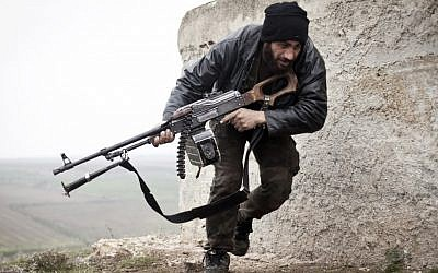 A Free Syrian Army fighter takes cover during fighting with the Syrian Army in Azaz, Syria on Monday. (photo credit: AP/Virginie Nguyen Huang)