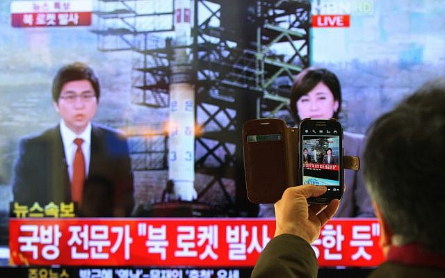A South Korean man uses his smartphone to take a picture of a television screen reporting news of North Korea's rocket launch, at Seoul Railway Station in Seoul, South Korea, Wednesday, December 12, 2012. The letters on the screen read 'North Korea's rocket launch seems to be successful.' (photo credit: AP/Ahn Young-joon)