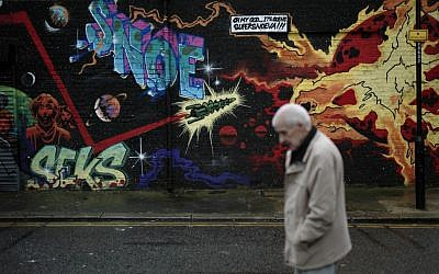 A man walks past street art in east London, Thursday, December 20, 2012. (photo credit: Matt Dunham/AP)