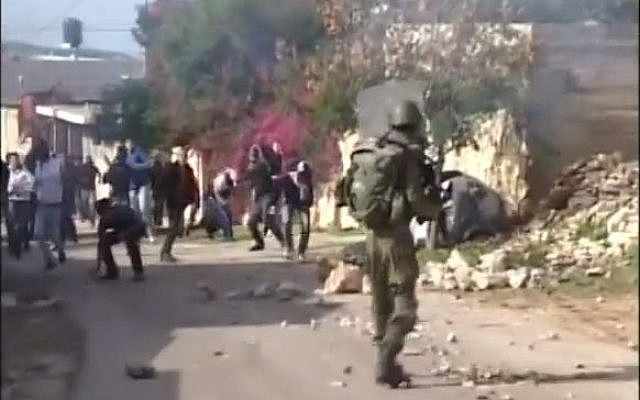 An IDF soldier confronts rioting Palestinians (photo credit: screen capture YouTube/MrDorkhan)