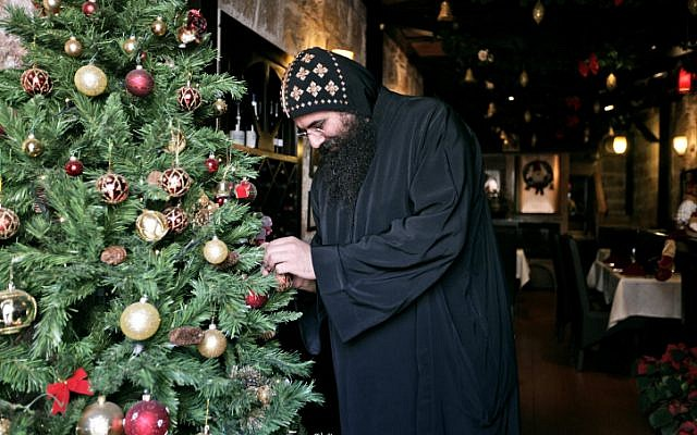 Coptic monk decorates a Christmas tree in the Old City of Jerusalem (photo credit: Abir Sultan/Flash90)