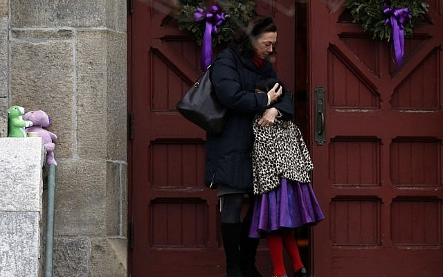 A woman hugs a young girl as they arrive for services at Trinity Church, Sunday, in Newtown, Connecticut (photo credit: AP/Jason DeCrow)