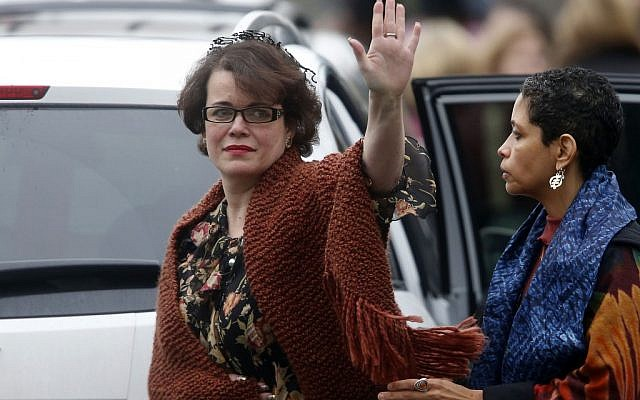 Veronique Pozner waves to the assembled press as she leaves after a funeral service for her son, 6-year-old Noah Pozner in Fairfield, Conn in December. The tree planting drive grew out of a request Pozner made in memory of her son. (photo credit: AP/Jason DeCrow)