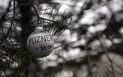 An ornament for Noah Pozner hangs on a tree at one of the makeshift memorials for the Sandy Hook Elementary School shooting, Monday, Dec. 17, 2012 in Newtown, Conn. Pozner was killed when a gunman walked into Sandy Hook Elementary School in Newtown Friday and opened fire, killing 26 people, including 20 children. (Mary Altaffer/AP)