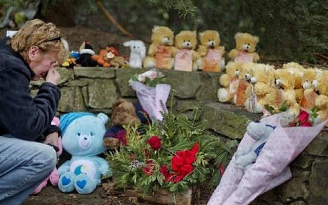Cheryl Girardi kneels beside 26 teddy bears, each representing a victim of the Sandy Hook Elementary School shooting, at a sidewalk memorial, on Sunday in Newtown, Connecticut (photo credit: AP/David Goldman)