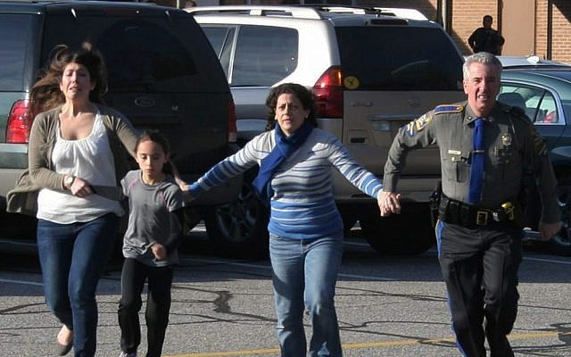 A police officer leads two women and a child from Sandy Hook Elementary School in Newtown, Connecticut, where a gunman opened fire, killing 26 people, including 20 children, December 14, 2012. (AP/Newtown Bee/Shannon Hicks)