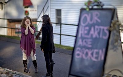 Shop owners Tamara Doherty, left, and Jackie Gaudet, right, meet outside their stores for the first time since being neighbors, just down the road from Sandy Hook Elementary School on Saturday. (photo credit: AP/David Goldman)
