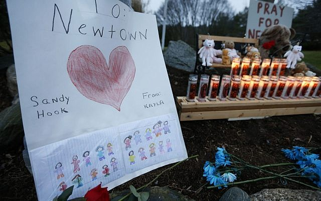 A child's message rests with a memorial for shooting victims, Sunday, December 16, in Newtown, Connecticut (photo credit: AP/Jason DeCrow)