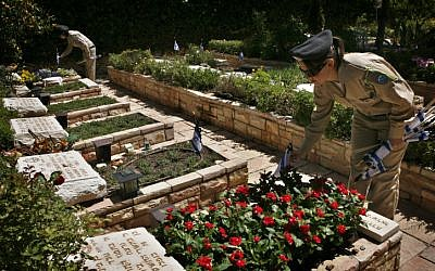 Soldiers place flags on graves at Mount Herzl Military Cemetary in Jerusalem to mark Memorial Day in 2012. (photo credit: Michal Fattal/Flash90)