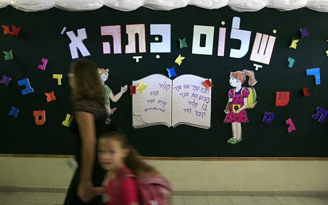 A mother and daughter walk by a sign greeting new first grade students in Jerusalem. (photo credit: Nati Shohat/Flash 90)