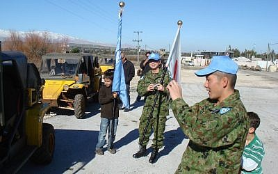 Japanese soldiers, part of the UN observer force in the Golan, take photos of jeeps near the Syrian border, in February 2009. (photo credit: Haim Azulay/Flash90)