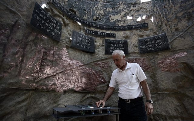 A man lighting a candle inside the monument in 2009. (photo credit: Abir Sultan/Flash90)